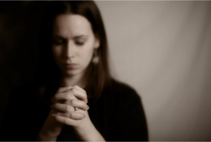 young woman praying intently